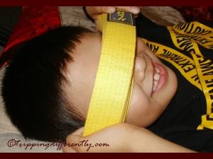 He's being goofy with his brand new yellow belt.