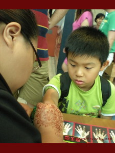Tobias getting a henna tattoo of a scorpion at the Maritime Museum.
